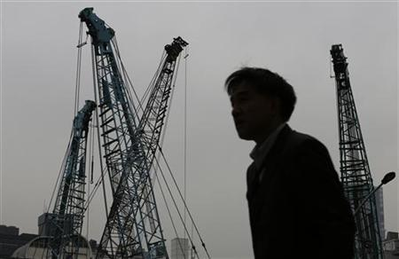 A man walks past cranes at a construction site in a business district in Tokyo December 28, 2012. Japan's factory output fell more than expected in November after a surprise jump in the previous month, keeping up pressure on the central bank to deliver further monetary stimulus as weak global trade weighs on the export-reliant economy. REUTERS/Kim Kyung-Hoon (JAPAN - Tags: BUSINESS CONSTRUCTION POLITICS)