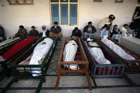 People gather around coffins of victims who were killed by twin explosions, during their funeral ritual at Nichari Imambargah Mosque in Quetta January 11, 2013. The death toll from a series of bombings in two Pakistani cities on Thursday, one of the bloodiest days in the country's history, has reached 114, police said Friday. Police officer Mir Zubair Mehmood said 82 people were killed and 121 injured in Quetta when a suicide bomber targeted a snooker club and a car bomb blew up nearby 10 minutes later. Nine police and 20 rescue workers were among those killed in the second blast. REUTERS/Naseer Ahmed