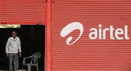 A man stands next to a shop painted with an advertisement for Bharti Airtel on the outskirts of Jammu December 11, 2012. REUTERS/Mukesh Gupta/Files