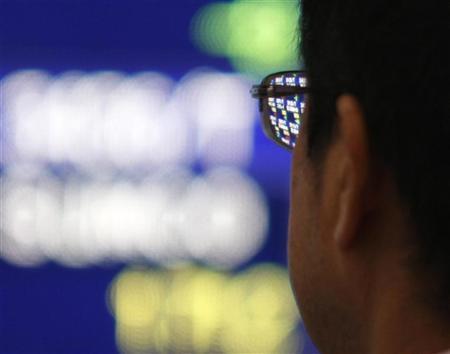 A man looks at a stock quotation board outside a brokerage in Tokyo November 2, 2009. REUTERS/Toru Hanai