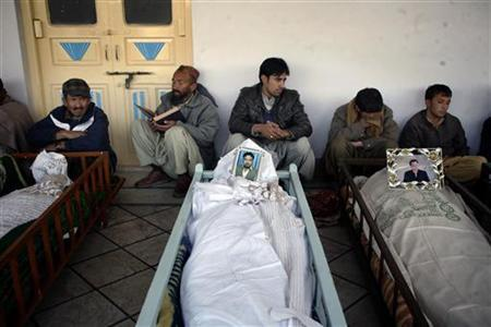 People gather around coffins of victims who were killed by twin explosions, during their funeral ritual at Nichari Imambargah Mosque in Quetta January 11, 2013. REUTERS/Naseer Ahmed