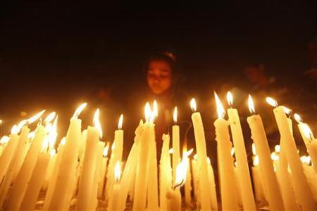 A girl lights candles during a candlelight vigil for a gang rape victim who was assaulted in New Delhi, in Kolkata December 29, 2012. REUTERS/Rupak De Chowdhuri/Files