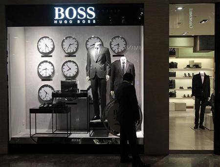 A man looks at a shop window outside the Hugo Boss showroom inside a shopping mall in Mumbai August 23, 2011. REUTERS/Danish Siddiqui
