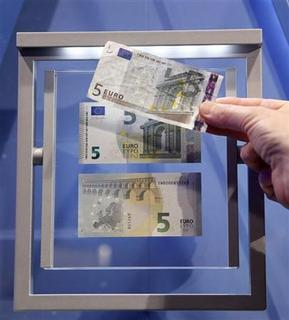A journalist compares the new 5 euro note with an old one (top) during a ceremony with Mario Draghi, President of the European Central Bank (ECB), in Frankfurt, January 10, 2013. REUTERS/Kai Pfaffenbach