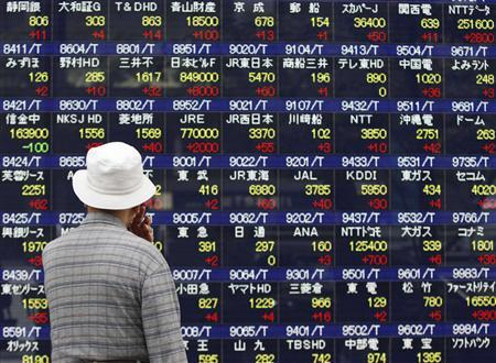 A man looks at an electronic board displaying market indices outside a brokerage in Tokyo October 17, 2012. REUTERS/Issei Kato