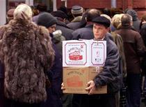 Мужчина с ящиками водки проходит мимо очереди в магазин ликероводочного завода Кристалл в Москве 12 февраля 2000 года. Инфляция в России с 1 по 9 января 2013 года составила 0,3 процента по сравнению с 0,1 процента за аналогичный период прошлого года, сообщил Росстат в пятницу. Наибольший прирост цен зафиксирован на водку, овощи и проезд в общественном транспорте. REUTERS/Alexander Natruskin