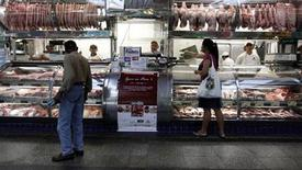Imagen de archivo de una mujer realizando unas compras en una canicería en el Mercado Muncipal de Sao Paulo, ene 11 2011. La industria de la carne porcina de Brasil prevé una expansión moderada en el volumen de las exportaciones en 2013 y un crecimiento más destacado en los precios externos, en un contexto de previsiones de mayor demanda y de entrada a nuevos mercados, dijo el viernes la asociación que agrupa al sector. REUTERS/Nacho Doce