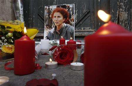 Flowers and candles are seen next to a portrait of late PKK activist Sakine Cansiz in front of the entrance of the Information Centre of Kurdistan, where three Kurdish women were found shot dead, in Paris January 11, 2013. REUTERS/Christian Hartmann