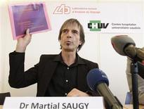 Director of the Swiss anti-doping laboratory Martial Saugy holds papers of a presentation during a news conference in Lausanne January 11, 2013. REUTERS/Denis Balibouse