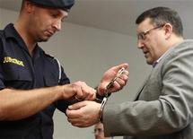 Policial retira algemas do austríaco Gottfried Kuessel (D) no tribunal em Viena, em junho de 2012. Uma corte austríaca condenou uma proeminente figura neonazista a nove anos de prisão por sua participação no lançamento de um site de extrema-direita que glorifica o nazismo. 26/06/2012 REUTERS/Heinz-Peter Bader