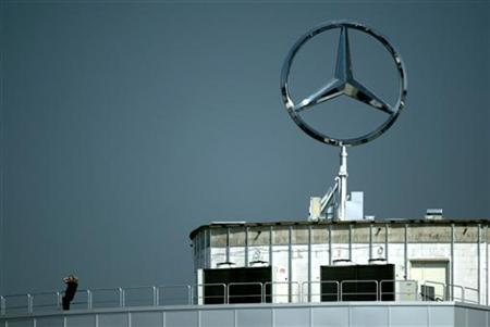 A spectator sits under a Mercedes-Benz symbol as he watches practice for the German Grand Prix at the Hockenheim circuit August 1, 2003. REUTERS/John Pryke/Files