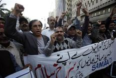 """Pakistani journalists chant slogans during a protest against bomb blasts in Quetta and condemn killings of members of the media, outside the press club in Karachi January 11, 2013. The banner reads in Urdu """"we wholeheartedly salute our martyr brothers"""". REUTERS/Athar Hussain"""