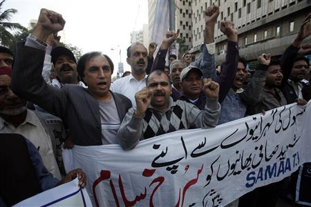 Pakistani journalists chant slogans during a protest against bomb blasts in Quetta and condemn killings of members of the media, outside the press club in Karachi January 11, 2013. The banner reads in Urdu ''we wholeheartedly salute our martyr brothers''. REUTERS/Athar Hussain