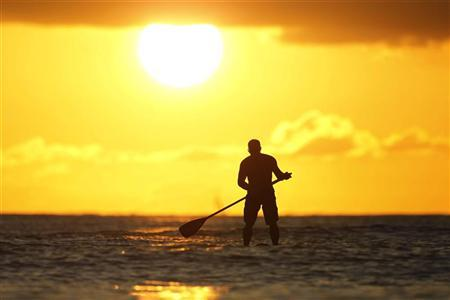 A paddle board rider surfs at sunset on New Year's Eve at Waikiki Beach in Honolulu, Hawaii, December 31, 2011. REUTERS/Jason Reed