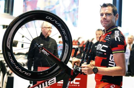 BMC Racing Team rider Cadel Evans of Australia holds his bike as he arrives at the cycling team's official presentation in Nazareth, near Ghent January 11, 2013. REUTERS/Francois Lenoir