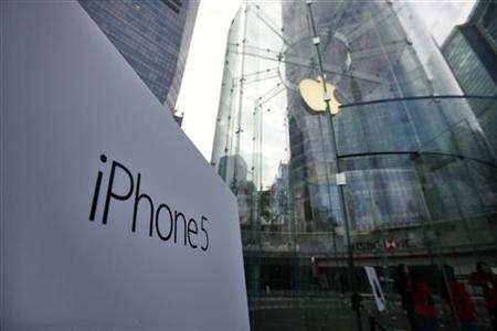 A sign of new iPhone 5 is seen at the entrance of an Apple Store in the financial district of Pudong in Shanghai December 14, 2012. REUTERS/Carlos Barria/Files