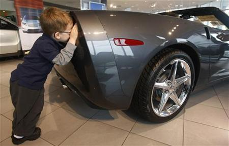 Ethan Toloza, 4, inspects tail lights of a new Chevrolet Corvette at Criswell Chevrolet in Gaithersburg, Maryland May 1, 2012. REUTERS/Gary Cameron/Files