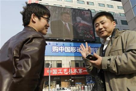 People talk about Chinese politics issues as a screen shows Xi Jinping speaking during a news conference, at Beijing's Wangfujing Street, November 15, 2012. REUTERS/Jason Lee/Files