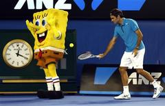Roger Federer of Switzerland hits a ball into the back of a man dressed as the cartoon character Sponge Bob Square Pants during Kids Tennis Day at the Australian Open tennis tournament in Melbourne, January 12, 2013. REUTERS/Tim Wimborne