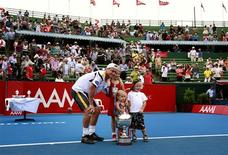 Australia's Lleyton Hewitt (L) poses with his children (L-R) Mia, Ava and Cruz and the trophy after he defeated Argentina's Juan Martin Del Potro in the final at the Kooyong Classic tennis tournament in Melbourne January 12, 2013. REUTERS/David Gray