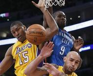 Oklahoma City Thunder's Serge Ibaka (C) fights for a rebound with Los Angeles Lakers Metta World Peace (L) and Robert Sacre of Canada during their NBA basketball game in Los Angeles, January 11, 2013. REUTERS/Lucy Nicholson
