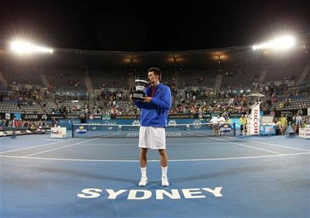 Bernard Tomic of Australia poses with the trophy after defeating Kevin Anderson of South Africa during their men's final match at the Sydney International tennis tournament January 12, 2013. REUTERS/Daniel Munoz