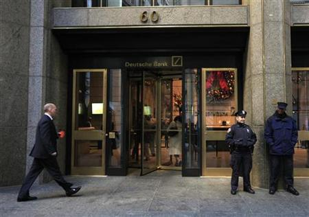 A New York City Police Officer stands beside a security officer at the entrance of a Deutsche Bank office in New York's financial district December 8, 2011. REUTERS/Brendan McDermid (UNITED STATES - Tags: BUSINESS CRIME LAW TPX IMAGES OF THE DAY)