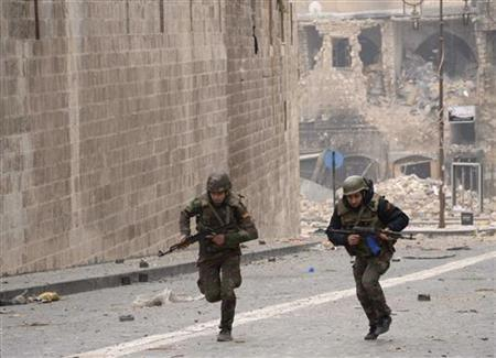 Syrian soldiers loyal to President Bashar al-Assad are seen running in Khan al-Wazir district in Aleppo city January 12, 2013. REUTERS/George Ourfalian (SYRIA - Tags: CIVIL UNREST POLITICS MILITARY TPX IMAGES OF THE DAY)