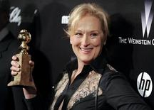 """Actress Meryl Streep shows off her Golden Globe award for the best performance by an actress in a motion picture - drama for her work in """" The Iron Lady"""" during her arrival at the The Weinstein Company after party following the 69th annual Golden Globe Awards in Beverly Hills, California January 15, 2012. Meryl Streep has won the most Golden Globes (eight), followed by Jack Nicholson (six) and Francis Ford Coppola, Shirley MacLaine, Rosalind Russell and Oliver Stone (five apiece). REUTERS/Gus Ruelas"""