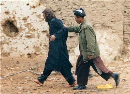 File photo of Lindh (L) being led away by a Northern Alliance soldier (R) near the Fort Qali-i-Janghi prison near Mazar-i-Sharif December 1, 2001 after he was captured among al Qaeda and Taliban prisoners following an uprising at the prison. REUTERS/STR-Files