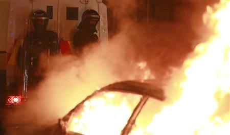 Police officers in riot gear look on as a hijacked car burns during rioting in East Belfast, January 12, 2013. Violent protests continue in Northern Ireland as loyalists renewed their anger against restrictions on flying the union flag from Belfast City Hall. REUTERS/Cathal McNaughton