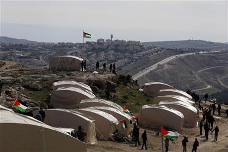 Palestinians, together with Israeli and foreign activists, stand near newly-erected tents in an area known as E1, near Jerusalem January 12, 2013. REUTER/Baz Ratner