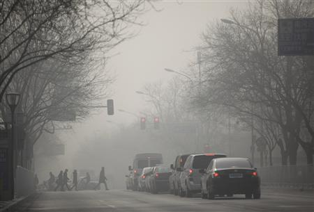 People walk during a heavily hazy winter day in central Beijing, January 12, 2013. REUTERS/Jason Lee