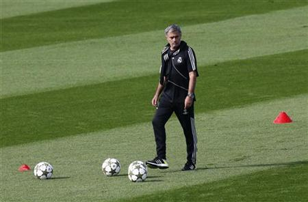 Real Madrid coach Jose Mourinho kicks a ball during a team training session near Madrid October 2, 2012. REUTERS/Andrea Comas/Files