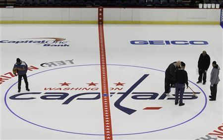 Workers put the finishing touches on the installation of the Washington Capitals logo at center ice during the laying down process of the playing surface at Verizon Center, the home of the NHL Washington Capitals, in Washington January 9, 2013.REUTERS/Gary Cameron