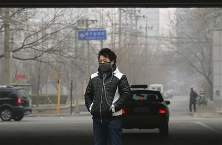 A man wearing a face mask stands on a street on a hazy winter day in central Beijing January 13, 2013. REUTERS/Petar Kujundzic