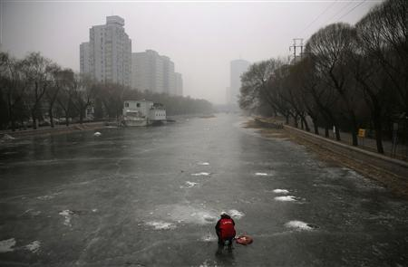 A man sits on a frozen canal and fishes on a hazy winter day in central Beijing January 13, 2013. REUTERS/Petar Kujundzic