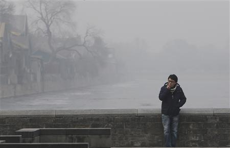 A man smokes near the Forbidden City on a heavy haze day in central Beijing January 13, 2013. REUTERS/Jason Lee