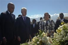 Haïti a commémoré samedi dans la sobriété le troisième anniversaire du séisme qui a décimé le 12 janvier 2010 la capitale Port-au-Prince et provoqué la mort de plus de 250.000 personnes. Le président haïtien Michel Martelly (à gauche) et l'ancien président américain Bill Clinton, émissaire des Nations unies en Haïti, ont participé à un dépôt de gerbes dans un cimetière situé sur une colline de la capitale. /Photo prise le 12 janvier 2013/REUTERS/Swoan Parker