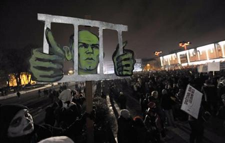 A protester holds up an image showing Slovenian Prime Minister Janez Jansa behind bars during anti-austerity and anti-graft protests in Ljubljana January 11, 2013. More than 5,000 Slovenians gathered in the centre of Ljubljana on Friday to protest against a corruption scandal that threatens to bring down the government. Slovenia's anti-corruption commission said earlier this week that Jansa had been unable to explain the source of some of his income in recent years. REUTERS/Srdjan Zivulovic (SLOVENIA - Tags: POLITICS BUSINESS)
