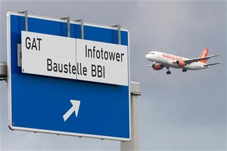 A planes approaching Schoenefeld SFX airport flies near a sign denoting the motorway exit to the building site of the Berlin Brandenburg international airport Willy Brandt (BER) in Schoenefeld outside Berlin January 11, 2013. Germans take pride in their engineering and organisational skills but their country's reputation for efficiency has been exploded by a farcical series of delays in building Berlin's new international airport. REUTERS/Thomas Peter (GERMANY - Tags: TRAVEL TRANSPORT)
