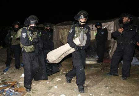 Israeli border police remove a Palestinian from an outpost of tents in an area known as E1, near Jerusalem January 13, 2013. Israeli security forces evacuated about 100 Palestinians early on Sunday from an outpost of tents pitched in an area of the occupied West Bank that Israel has earmarked for a new settlement. REUTER/Ammar Awad (WEST BANK - Tags: CIVIL UNREST RELIGION POLITICS TPX IMAGES OF THE DAY)