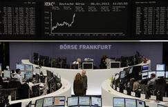 Traders are pictured at their desks in front of the DAX board at the Frankfurt stock exchange January 8, 2013. REUTERS/Remote/Lizza David (GERMANY - Tags: BUSINESS)