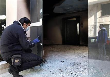 A police expert searches for evidence at the damaged entrance of a building in Athens January 13, 2013. Petrol bombs were thrown at the Athens home of the brother of Greece's government spokesman early on Sunday, causing minor damage but no injuries, police said. REUTERS/John Kolesidis
