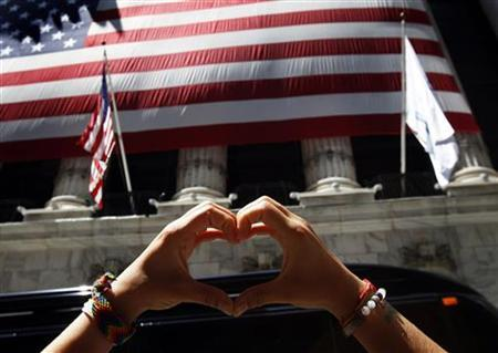 A woman does yoga outside the New York Stock Exchange August 8, 2011. REUTERS/Shannon Stapleton/Files