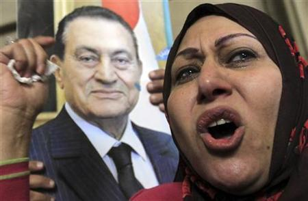 A supporter of ousted former Egyptian President Mohammed Hosni Mubarak stands near a poster of him at a protest outside a High Court in Cairo December 23, 2012. REUTERS/Mohamed Abd El Ghany/Files