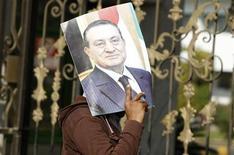 Apoiador do presidente egípcio deposto Hosni Mubarak segura sua foto do lado de fora do Hospital das Forças Armadas Maadi, onde Mubarak está atualmente detido, no Cairo. 13/01/2013 REUTERS/Mohamed Abd El Ghany