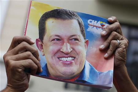 A supporter of Venezuela's President Hugo Chavez holds up a picture of him during the inauguration of the National Assembly in Caracas January 5, 2013. REUTERS/Carlos Garcia Rawlins