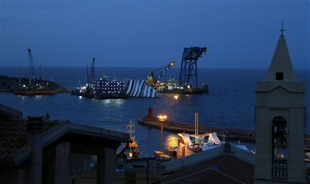 The capsized cruise liner Costa Concordia is pictured surrounded by cranes outside Giglio harbour January 12, 2013. REUTERS/Stefano Rellandini