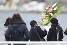 Los supervivientes del desastre del Costa Concordia y los familiares de las 32 personas que murieron volvieron a la isla italiana de Giglio el domingo para conmemorar el primer año del naufragio del crucero de lujo. En la imagen, familiares de las víctimas lanzan flores al mar, en Giglio, el 13 de enero de 2013. REUTERS/Tony Gentile